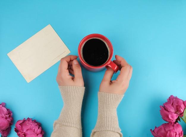 Rote molkereitasse mit schwarzem kaffee in weiblichen händen und einem strauß roter pfingstrosen