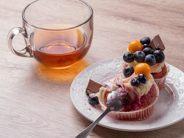Rote muffins mit blaubeeren und schokolade auf einem holztisch. tee und muffins zum frühstück. leckeres frühstück zu hause.