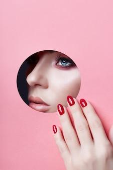 Rote nägel des prallen lippenroten make-up des schönheitsgesichtes einer jungen frau in einem runden schlitzloch des rosa papiers. frau mit den prallen lippen, den manikürenägeln, dem gesicht und der hand des schönen make-up