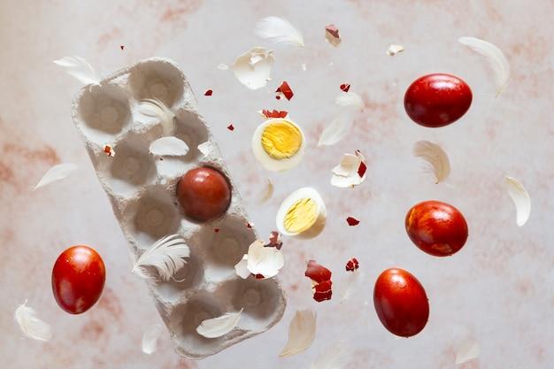 Rote natürliche farbstoff-ostereier, die mit federn auf pastellbeige hintergrund fliegen