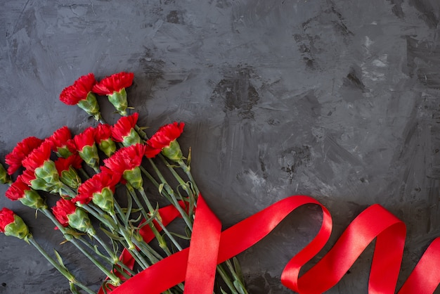 Rote nelken auf grauem / schwarzem hintergrund, flach legen, draufsicht mit kopienraum