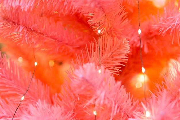 Rote niederlassungen des weihnachtsbaums mit gelben leuchten. dekorative fichte
