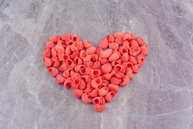 Rote nudeln in herzform auf der marmoroberfläche