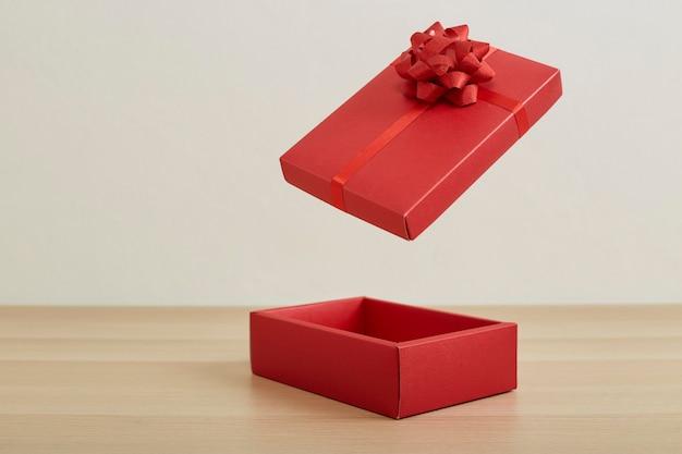 Rote offene geschenkbox mit rotem band auf hölzernem tischhintergrund