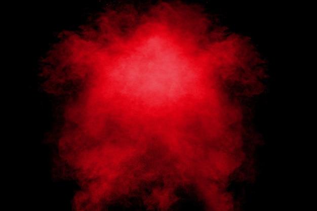 Rote orange farbpulver-explosionswolke auf schwarzem hintergrund.