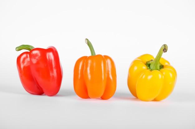 Rote, orange und gelbe paprika auf weiß
