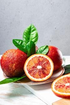 Rote orangen ganz und halb auf einem teller, vertikales foto.