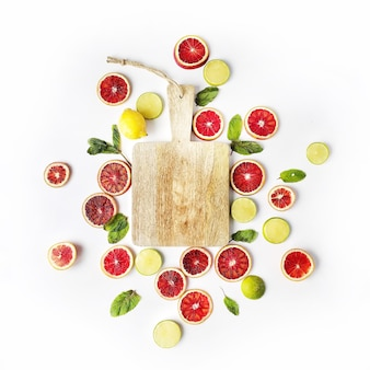 Rote orangen, gelbe zitronen, grüne limetten, minze und schneidebrett isoliert auf weiß