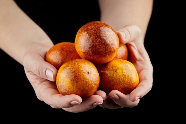 Rote orangen in den händen an der schwarzen wand