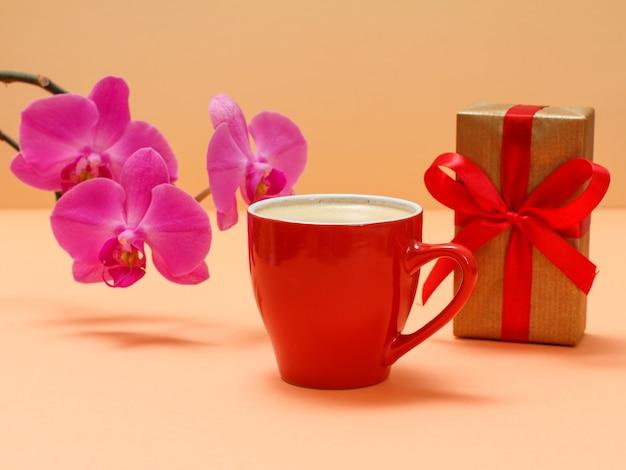 Rote orchideenblüten mit tasse kaffee auf beigem hintergrund.