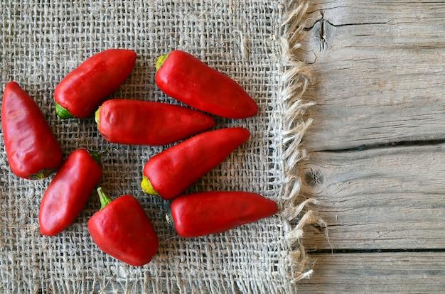 Rote organische paprikapfeffer auf einem leinwandstoff auf altem holztisch