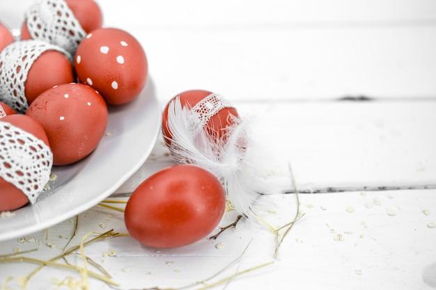 Rote ostereier auf einem weißen teller und auf weißem gebundenem spitzenband, nahaufnahme