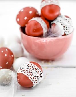 Rote ostereier auf weißem gebundenem spitzenband, nahaufnahme