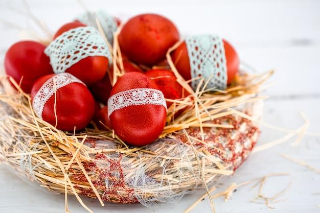 Rote ostereier in einem nest des heus