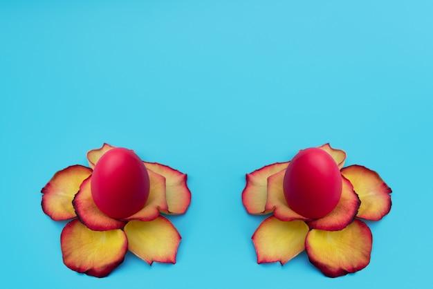 Rote ostereier stehen in gelben blüten aus rosenblättern auf blau