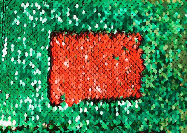 Rote pailletten in den dunklen glitzernden grünen reflektierenden pailletten