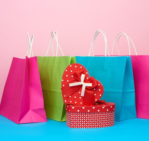 Rote papierbox mit einem geschenk und papiertüten zum einkaufen