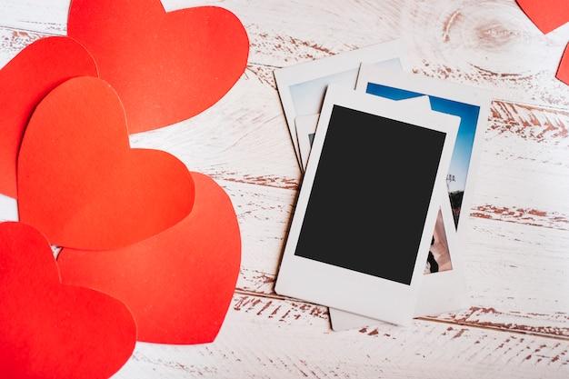 Rote papiere mit fotos auf dem tisch