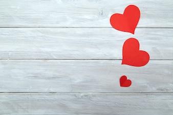 Rote Papierherzen am weißen hölzernen Valentinstag