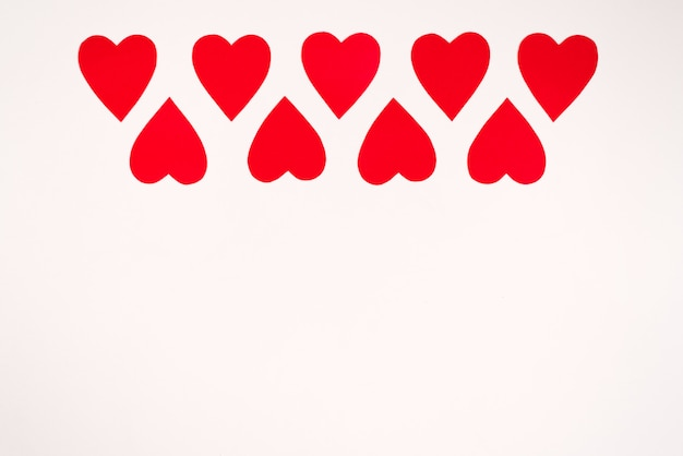 Rote papierherzen auf weißem hintergrund, grenze, kopienraum. valentinstag-weihnachtskarte