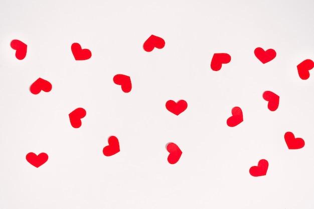 Rote papierherzen auf weißem hintergrund. weihnachtskarte zum valentinstag. tag der liebe