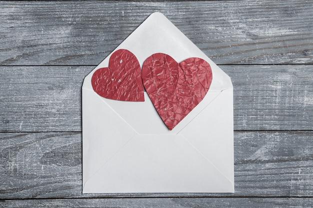 Rote papierherzen mit umschlag auf holzoberfläche