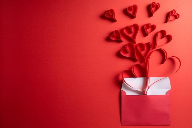 Rote papierherzen spritzen heraus vom umschlag. liebes- und valentinstagkonzept.