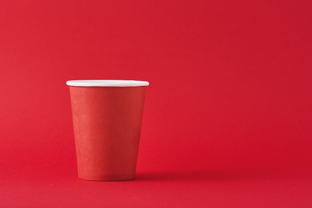 Rote papierkaffeetasse auf rotem hintergrund mit kopienraum. minimalismus-stil