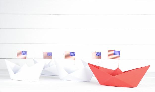 Rote papierschiff mit usa amerika flagge führt. unabhängigkeitstag usa, happy independence day, 4. juli.