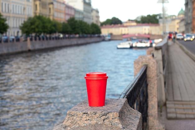 Rote pappbecher kaffee auf geländer am flussufer
