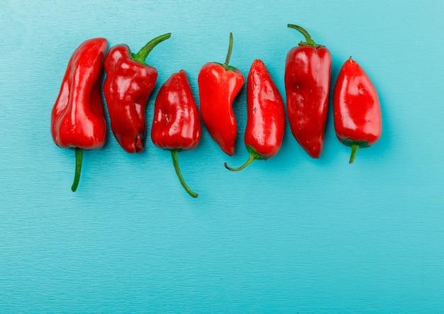 Rote paprika auf blauer wand, draufsicht.