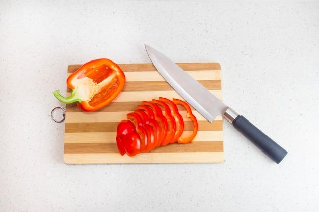 Rote paprika auf dem schneidebrett. die zubereitung von gesunden lebensmitteln.