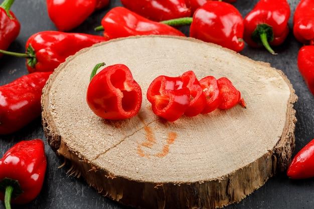 Rote paprika auf einer hohen ansicht des holzstücks auf einer grungy grauen wand