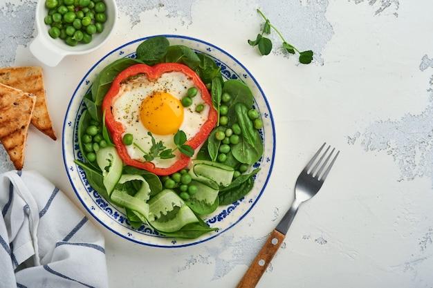 Rote paprika gefüllt mit eiern, spinatblättern, grünen erbsen und mikrogrün auf einem frühstücksteller auf hellgrauem tischhintergrund. ansicht von oben.
