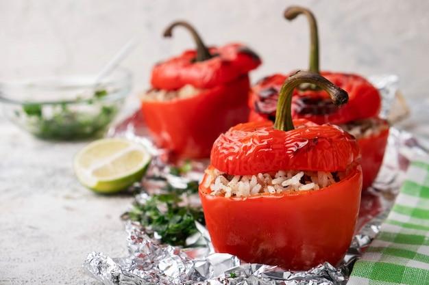 Rote paprika gefüllt mit fleisch, reis und preiselbeeren