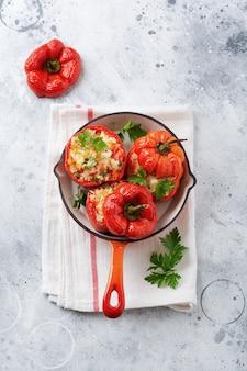 Rote paprika gefüllt mit reis und gemüse auf gusseisenpfanne auf grauem betonhintergrund.