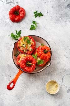 Rote paprika gefüllt mit reis und gemüse auf gusseiserner pfanne auf grauem betonhintergrund