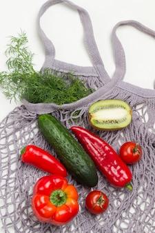 Rote paprika, gurke und halbe kiwi auf grauem baumwollgewebe. bund dill. weißer hintergrund. flach legen