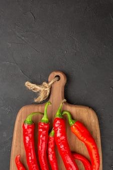 Rote paprika in der oberen hälfte auf einem schneidebrett am unteren rand des schwarzen tisches