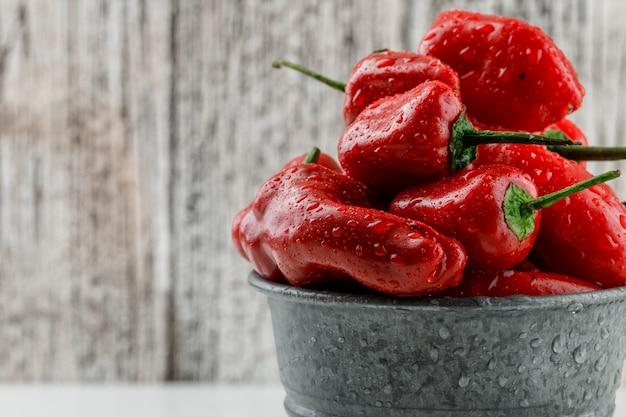 Rote paprika in einem mini-eimer auf weißer und hölzerner schmutzwand, nahaufnahme.