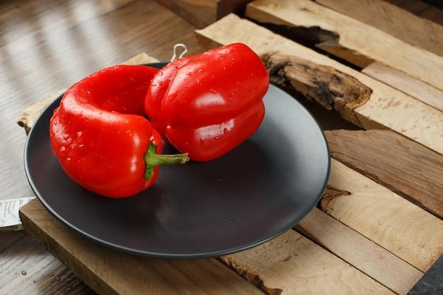 Rote paprika in einem schwarzen teller auf einem stück holz.