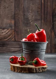 Rote paprika mit holzstück in einem minieimer auf grungy und steinfliesenwand, seitenansicht.