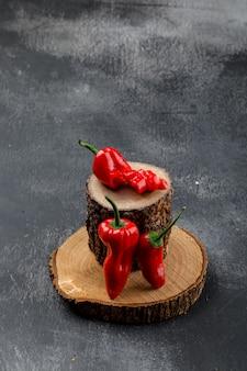 Rote paprika mit holzstücken auf grungy grauer wand, hohe winkelansicht.