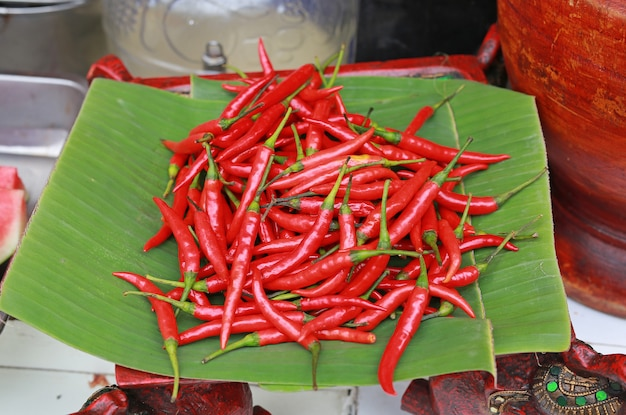 Rote paprikas auf bambusblatt.