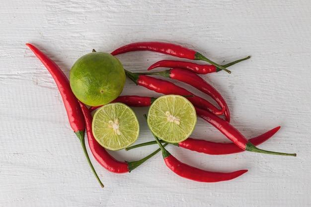 Rote paprikas und zitrone für das kochen des thailändischen lebensmittels auf weißem holztisch