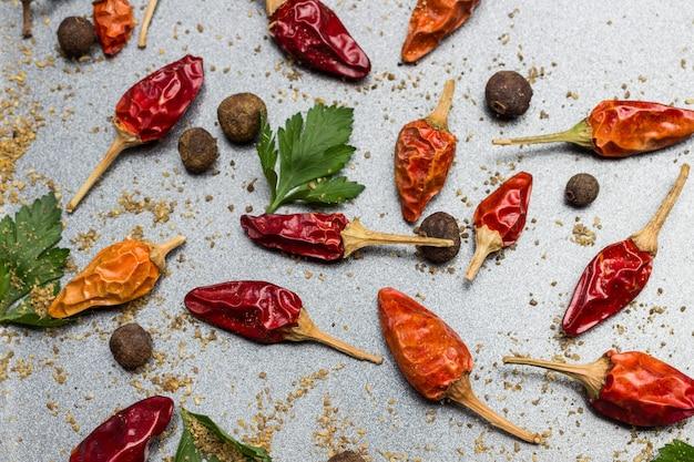 Rote paprikaschoten und gemahlenen koriander trocknen. piment und petersilienblätter. metallischer hintergrund. flach legen