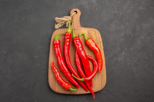 Rote peperoni der draufsicht auf einem schneidebrett in der mitte des schwarzen tisches mit kopierraum