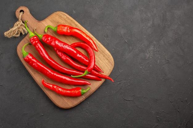 Rote peperoni von oben auf einem diagonalen schneidebrett auf der linken seite des schwarzen tisches mit kopierraum