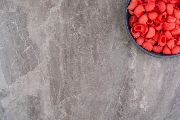 Rote pfeifennudeln in einer schüssel auf dem marmor.