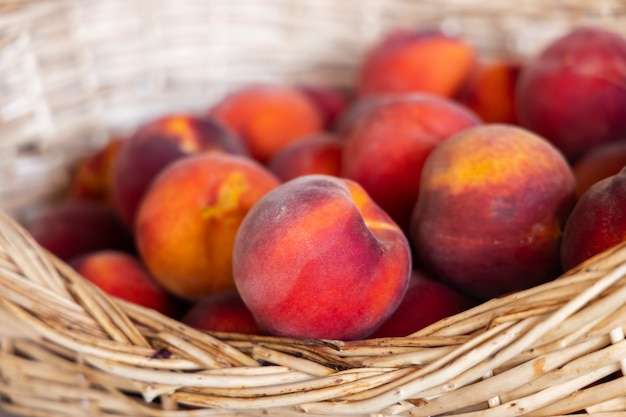 Rote pfirsiche im weidenkorb